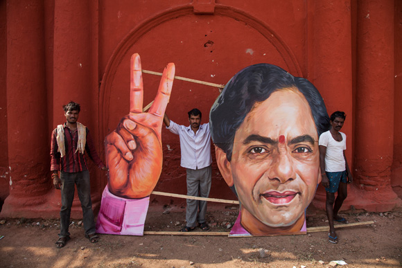 Workers deconstruct an image after the signing-in ceremony of the Chief Minister of India's newest state
